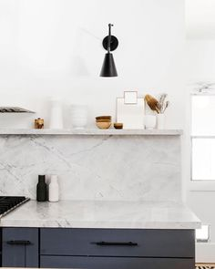 Love the marble backsplash and shelf in this gorgeous design by Erin Melkonian Designs , photographed by Ellie Koleen Photography, including our Articulated Tilt Cone Sconce in matte black. Modern Kitchen Design, Interior Design Kitchen, Kitchen Decor, Scandinavian Kitchen Backsplash, Modern Kitchen Backsplash, Minimal Kitchen, Countertop Backsplash, White Countertops, Marble Kitchen Countertops