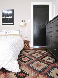 Black door, white architrave, carpet, bedside lighting