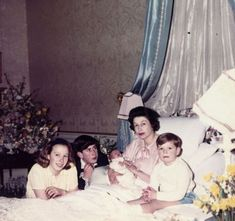 Queen Elizabeth in bed after the birth of Prince Edward in 1964. Surrounding her, are her 3 children, Prince Charles, Princess Anne and Prince Andrew.