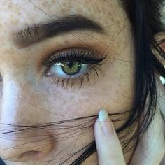 Black hair, green eyes, and freckles