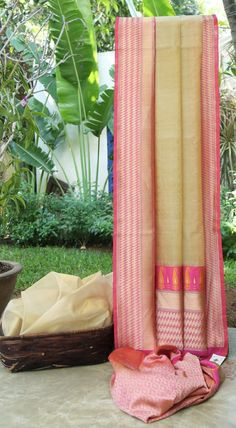 This Benares kora is in a plain pale beige. The border is in pink with gold zari, silver zari, magenta and meena work. The pallu is in pink with gold zari work making it a simple and elegant piece.
