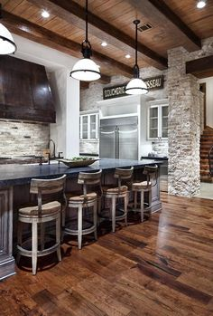 Kitchen, natural stone walls, wood floors, counter stools from wine barrels? - The Stylish Academic