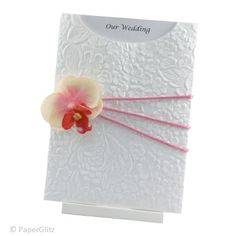 COCONUT ICE A summery invitation featuring an Embossed White Roses pocket decorated with a dusty pink cord ribbon and a cream and pink silk phalaenopsis orchid. The insert is on Ice Gold card and simply slides out to reveal your special announcement. Completed Invitation with Envelope Box: $7.95 https://www.facebook.com/NextChapterWeddingInvitations