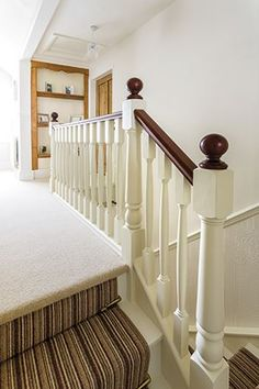 Painted white newel & spindles with cream landing carpet & multi coloured stair runner.