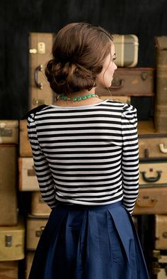 Navy + stripes  Very classic, very versatile.  The stripes add a nice dimension, the skirt provides a nice solid bases.  I'd probably see this with navy or black flats or maybe a small heel.  Hair up adds more to the feminine direction, making the whole outfit very classy but still flirty.