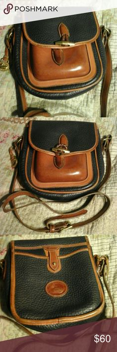 Dooney & bourke crossbody Black and tan/brown vintage crossbody with brass toggle closure. It good shape. Has been used . Has long strap with it. Dooney & Bourke Bags Crossbody Bags