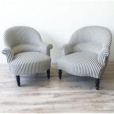 Description Companion pair of 19th-Century French Napoleon III Armchairs in Ralph Lauren navy-blue mattress ticking with scrolled arms and ebonized turned legs c. 1870. Seat height measures 14 in. One chair features a serpentine seat rail, one with curved seat rail.