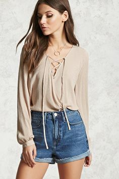 A textured woven top featuring a lace-up surplice neckline, a draped front, long sleeves with button cuffs, and a shirred back panel.