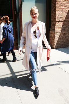 Jaime King wears a tank top, blush pink coat, distressed skinny jeans, pointed-toe oxfords, cat-eye sunglasses, and a red clutch