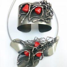 Oryginalny komplet biżuterii satynowanej z listkami i kamieniami imitującymi koral. W całości wykonany ręcznie z alpaki, miedzi i mosiądzu. Naszyjnik zawieszony jest na stalowych linkach o długości 46 cm.