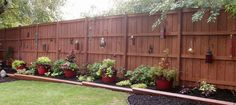 love the high Privacy Fence with hanging lanterns. large pots in front add a pop of color!