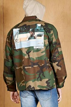 A woven army jacket by Vintage Wear LA™ featuring a camouflage print, an Ice Cube graphic on the back, a buttoned front, basic collar, long button cuff sleeves, and buttoned flap pockets on the chest and front.