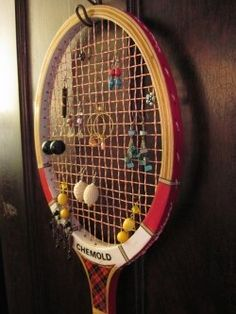Simple steps in the game called organization: 1) Hang old tennis racket; 2) Hang earrings; 3) Done.