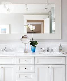 subway tile wrapped around room. calcutta marble vanity top. large framed mirror.