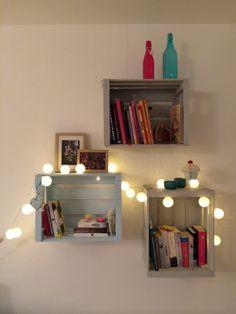 1.) Was ist Deine Lieblingsecke in Deinem Zuhause und warum?  Die Obstkisten eigenen sich prima als Bücherregal. Gestrichen sind sie in einem mittleren Grauton, einem helleren Grauton und eine Kiste in Mint. Die bunten Bücher und die zwei bunten Flaschen machen das Ganze noch farbenfroher. Außerdem ist die Ecke über den Winter noch mit einer Lichterkette dekoriert.