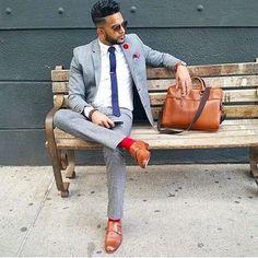 Men's Brown Sunglasses, Burgundy Pocket Square, Navy Polka Dot Tie, White Dress Shirt, Grey Wool Blazer, Red Socks, Brown Leather Messenger Bag, Grey Wool Dress Pants, and Brown Leather Double Monks