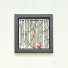 Wild and free. Hand-cut birch trees, small fox silhouette and text in white, dark gray, and poppy red. Background is gray paper. Set in a black frame.