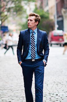 清涼感あるメンズ 紺色スーツの着こなし例。ストライプのネクタイをアクセントに。