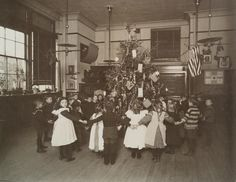 Children in New York City holding hands in a circle around Christmas tree.