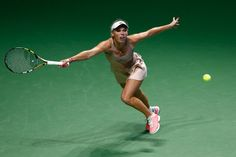 Caroline Wozniacki of Denmark in action against Maria Sharapova of Russia during day two of the BNP Paribas WTA Finals tennis at the Singapore Sports Hub on October 21, 2014 in Singapore.