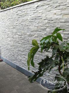 Verwerking steenpanelen - natuursteenstrips Grijs Kwartsiet op een buitenmuur.