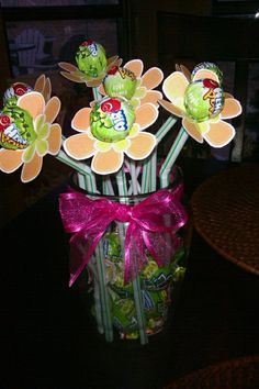 lolli pop flower arrangement i made for my friend's baby shower. it's easy and all you need to do is put the lolli pop ends through straws and get a cute flower paper pattern to cut out and stick it through the bottom end of the lolli pop. fill the jar with remaining lolli pops to look full.