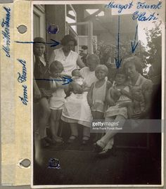 Anne held by a woman (Mrs. Dassing?), being welcomed by her sister Margot's friends on a balcony, with names written on the photograph, Marbachweg, Frankfurt am Main, Germany. Anne's mother, Edith Frank-Hollander, is standing in back and Margot is sitting on their domestic servant Kathi's lap to the left.
