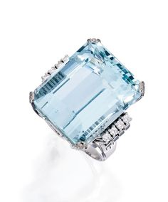18 KARAT WHITE GOLD, AQUAMARINE AND DIAMOND RING Set with an emerald-cut aquamarine weighing 57.54 carats, flanked by eight round diamonds weighing approximately .25 carat