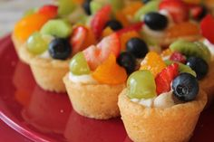 Fruit Cookie Cups 24 Mini-Cups 1 Pac Pillsbury Refrig Sugar Cookie Dough 8oz cream cheese, soft 1/4c sugar 1/2t vanilla Fruits, chop Oven/350 & grease mini cups Slice cookie dough into 24 parts, roll into a ball, & place in each muffin cup mold  dough into  shape of the muffin tin,  Bake 350/12 min  Once cool, transfer to tray Mix cream cheese, sugar, & vanilla. Pipe into the cooled cookies. Top with fruit. Fruit Salad, Easy Desserts For Kids, Kids Fruit, Recipes For Children, Fruit Salads