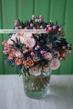 Необычный свадебный букет из пионовидных кремовых роз , синих ягод вибурнума, персиковых ягод гиперикума, коричневых роз и эрингиума