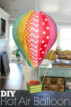 DIY hot air balloons - attach part of Styrofoam or plastic cup to bottom of paper lantern, add fabric strips and scraps using hot glue and mod podge, suspend berry basket with yarn. for kids' room Hot Air Balloon Paper, Diy Hot Air Balloons, Hot Air Ballon Diy, Balloon Crafts, Balloon Decorations, Crafts With Balloons, Balloon Party, Papier Diy, Paper Crafts