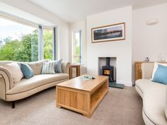 The stylish living room with picture windows, elegant furnishings and log burning stove.