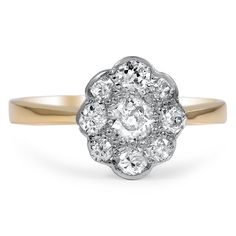 A ravishing old European cut center diamonds shines from within the floral-inspired halo