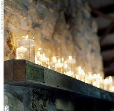 Floating candles in glass jars adorn a fireplace mantle or shelf... So simple and elegant. Vary the amount of water in each jar for an even more beautiful effect.