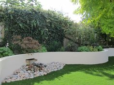 Garden Design by Sheila Hassock. Like the idea of a water feature in the retaining wall =)