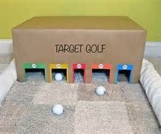 Target golf  For this game you will need ◦ 1 large box with 5 cut outs and colored and numbers as shown in the image above ◦ 3 golf balls or small plastic balls ◦ 1 toy golf club