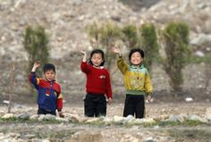 North Korean children wave to people on a Chinese tourist boat on the banks of Yalu River near the Chongsong county of North Korea, opposite the Chinese border city of Dandong, May 8, 2011.