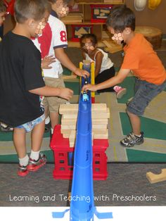 Children using their problem solving skills when making ramps in the construction center.
