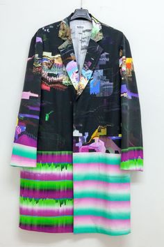 Coat by NukemeShop on Etsy. This is a coat shaped as a lab coat, designed by Nukeme and Ucnv. Nukeme makes the clothing work. Ucnv made the textile pattern with glitch images. This product is made to order and shipping from Tokyo. It is made of 100% cotton, with digital textile printing.