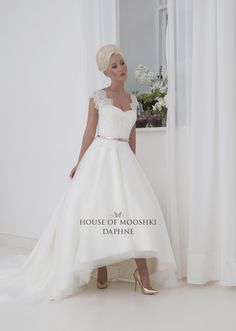 Daphne - Gorgeous vintage Haute Couture inspired high/low wedding dress. Beautiful and elegant with a 2 metre train, Daphne is one of our favoruites here at Mooshki HQ. Lace applique covers the shoulders and cascades over the sides of the bodice, contouring the waist and showing off your figure. Calf length at the front with a sweeping train to the back, layers and layers of tulle flare out and create a dramatic yet simple silhouette.