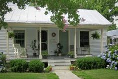 Love this porch and tin roof.  The hydrangeas also caught my eye.  (Edenton NC Cottage For Sale)