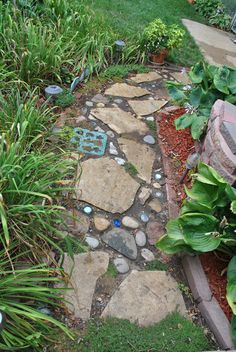 A work in progress-Add jar lids, colored jars (upside down), tiles, glass candle holders, etc to a garden path. Fill the cracks with Stepables and succulents