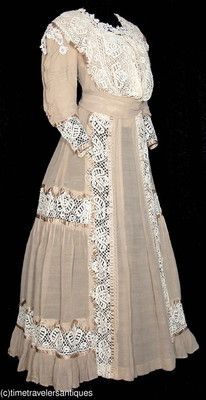 1905 lady's two piece beige French silk crepe dress that is embellished with mixed bobbin and chemical lace and trimmed in a bronze silk satin. The stayed bodice is lined in silk, with ruched sleeves, a fashionable pigeon breast, and a blind front hook and eye closure. The gored skirt has matching inset lace and silk satin ribbon trim, accent pleats, an inverted pleat to the back, and a pleated ruffle at the hem.  Offered on Ebay