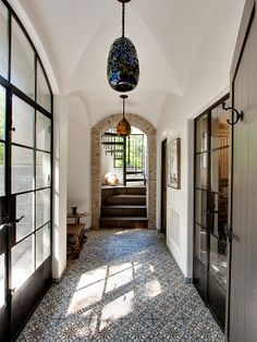 Mosaic tile, hand blown glass light fixtures, vaulted ceiling, exposed brick archway,  and black French doors