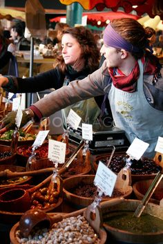 People serving from an olive stall at Borough Market, London, England