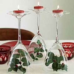 Christmas centerpieces Take some wine glasses, and some twigs with small fruit in them. Put the twig in the glass and invert it as shown in the picture. Get a small colorful candle and place it on the base of the glass. Place them in a group of two or three with different color candles all around the table. #Christmas Ideas #Holiday decorations
