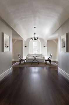White, clean, simple sitting area, arched ceiling, white and wood furniture mix