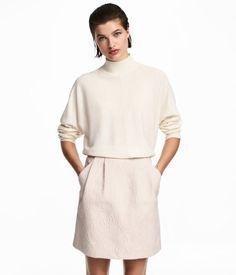 Ljusbeige/Paisley. En kort kjol i strukturvävd kvalitet. Kjolen har hög midja med lagda veck upptill. Dragkedja bak och sidfickor. Ofodrad.