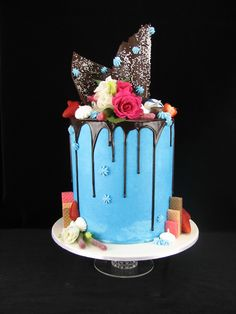 I really enjoyed working with lots of new elements and techniques for this delightful engagement cake. It is a double barrel red velvet cake filled with white buttercream and covered in blue buttercream and dripping dark chocolate ganache. On top I have added sculpted chocolate shards, meringue kisses, fresh strawberries, fresh flowers, wafers, chocolates and sour worms. Check out my page at www.facebook.com/cakesbyleannerhodes