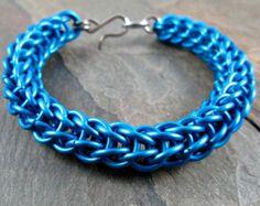 Esta pulsera de chainmaille impresionante fue mano tejida en el tejido de caña/paralelo con anillos de brillante plata, oscuro azul y amarillo de